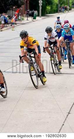 STILLWATER, MINNESOTA/USA - JUNE 18, 2017: Pro women cyclists race downhill at the 2017 North Star Grand Prix Stillwater Criterium. Emma White (lead racer in yellow) is the overall race winner.