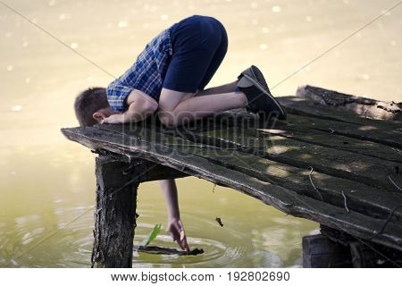 Thoughty boy on pier near pond and playing with small boat from bark and leaf. A little kid thinks and looks at the pond. Dream positive atmosphere, sunny day.