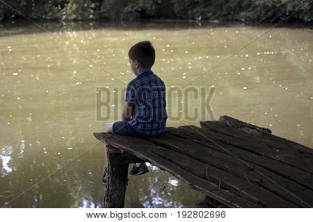 Dreamy boy sitting on wooden pier at pond. Little kid thinks and looks at pond. Dream positive atmosphere, sunny day.