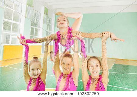 Close-up portrait of happy preteen girls carrying out their routine in rhythmic gymnastics tournament