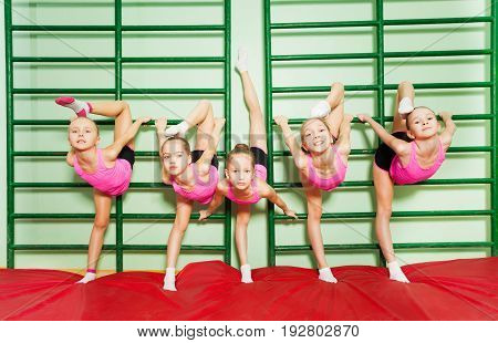 Group of 11-12 years old girls stretching near wall mounted gym ladder during gymnastic class