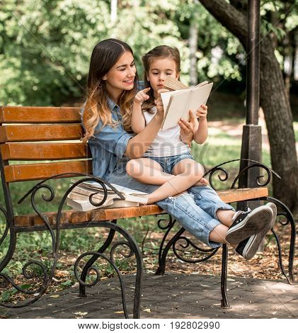 Mom and daughter on a bench read a book in the park, the concept of family relations, and family values