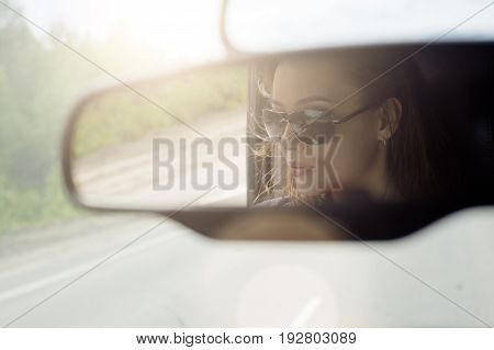 Reflection of a beautiful girl in the car mirror. She travels by car in Sunny weather