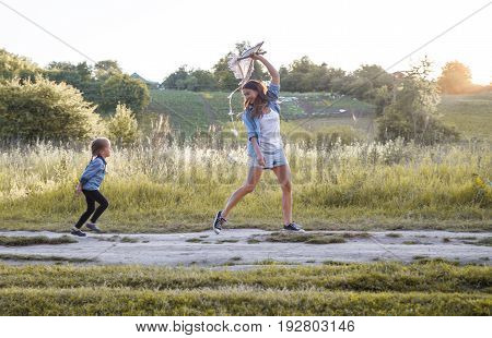 Young mother with daughter playing with a kite on the nature of the concept of family values
