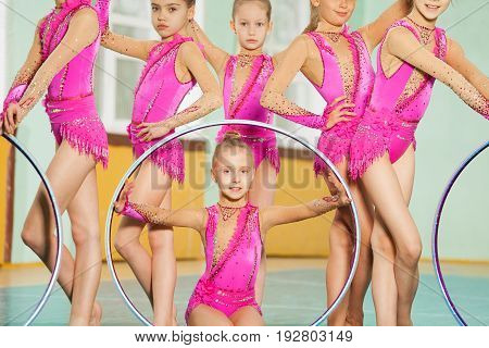Close-up portrait of preteen girls in pink leotards posing with hoops during rhythmic gymnastics competition