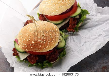 fresh tasty burger on white paper on grey background