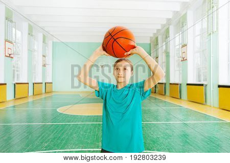 Portrait of preteen girl practicing her basketball, tossing the ball in the rim in sports hall