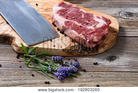 Freshly cut raw beef with marbled fat on carving board with spices and herbs