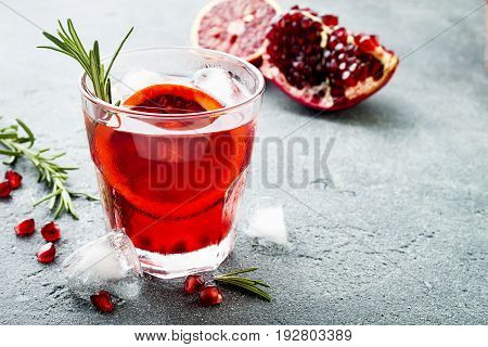Red cocktail with blood orange and pomegranate. Refreshing summer drink on gray stone or concrete background. Holiday aperitif for Christmas party. Copy space