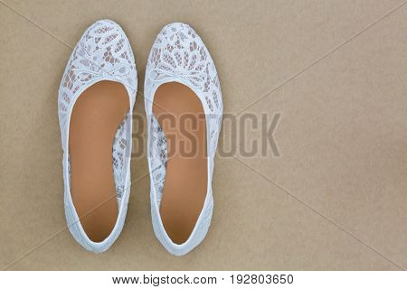 Top view of popular white floral lace ballet flat slip on shoes on brown background
