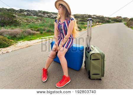 Sad woman sitting on suitcase on the road