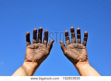 Two male hands raised up against the blue sky