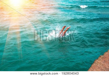 A young man's legs disappearing as he dives into the in a refreshing sea, ocean, On a hot summer day