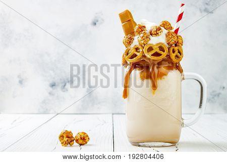 Salted caramel indulgent exreme milkshakes with brezel waffles popcorn and whipped cream. Crazy freakshake food trend. Copy space