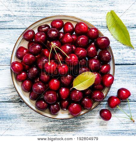 Fresh Cherry On Plate On Wooden Blue Background. Fresh Ripe Cherries. Sweet Cherries