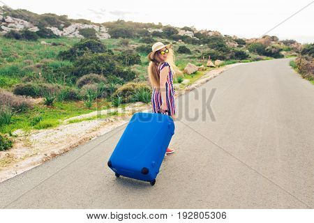 Freedom, travel, vacation and summer concept - Traveler woman walking on the road with suitcases and laughs.