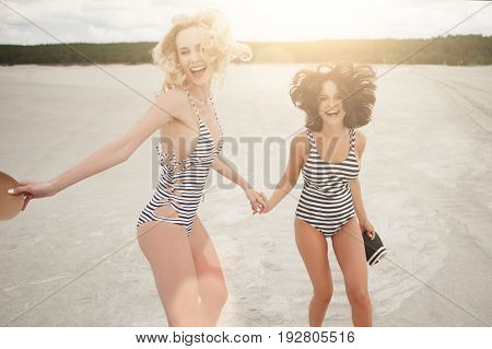 Two girls in bathing suits who were in love with each other having fun on the beach evening, lots of laughter and happiness