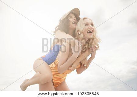 Two beautiful girls in bikinis laughing and having fun on the beach