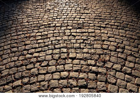Gloomy old cobblestone pavement. Beautiful stone background