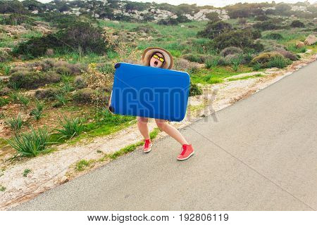 Young woman with blue suitcase making funny faces outdoors.