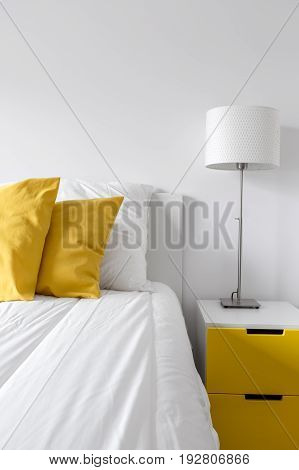 White Bedroom With Yellow Sidetable