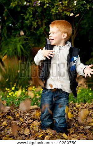 Happy red haired young preschool boy playing in autumn leaves
