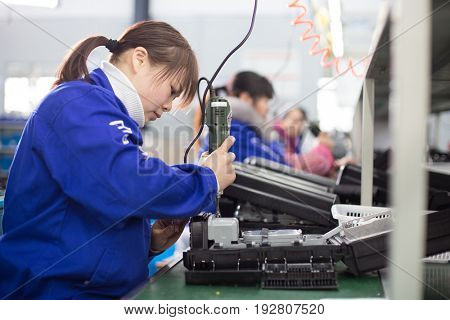 jinhua,china-Jan 23,2017:young woman worker working on production line in manufacturing factory