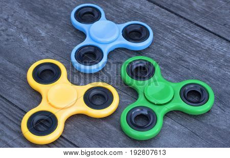 Three fidget spinner stress relieving toy on a wooden background.
