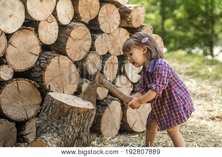 Little girl cuts the tree near the deck wood concept of children's recreation