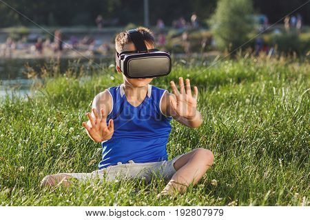 Boy Plays Game With Virtual Reality Glasses Outdoors