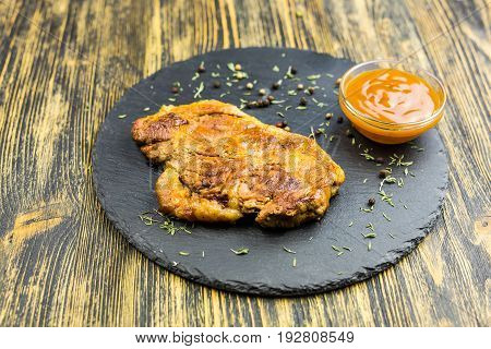 Grilled pork steak on black stone background