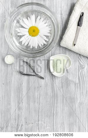 Spa composition on wooden desk with chamomile, salt, towel and manicure set copyspase top view.