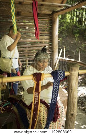 CHEROKEE, USA-JUNE 17, 2017: Unidentified Cherokee woman makes cloth in the traditional manner in Cherokee, North Carolina
