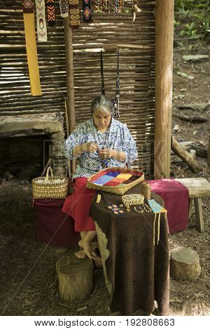 CHEROKEE, USA-JUNE 17, 2017: Unidentified Cherokee woman does traditional beadwork in Cherokee, North Carolina