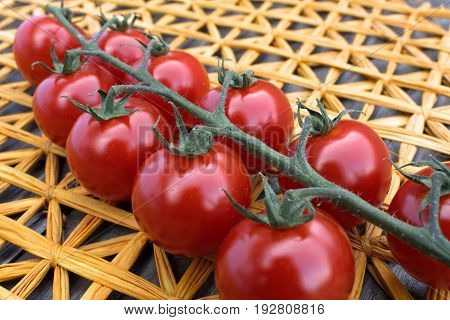 Fresh cherry tomatoes on a background of a straw mat.