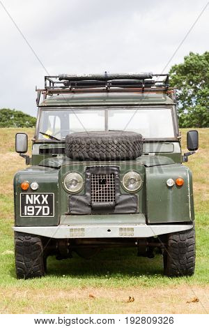 BEAULIEU HAMPSHIRE UNITED KINGDOM - JUNE 25 2017 Land Rover day with many varieties of Land Rovers including this Land Rover Series 2 in a green color parked on the grass on a cloudy day.