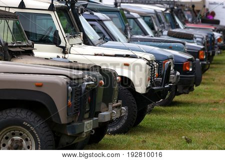 BEAULIEU HAMPSHIRE UNITED KINGDOM - JUNE 25 2017 Land Rover day with many varieties of Land Rovers including the Defender Discovery and Range Rover all parked in a row on the grass with selective focus.