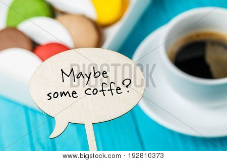 Wooden board with inscription on background of macaroons and cup of coffee. Focus on board