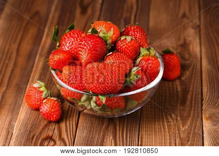 Image of fresh ripe strawberry in cup on wooden table