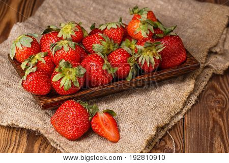 Picture of fresh ripe strawberries on wooden plate, linen fabric closeup