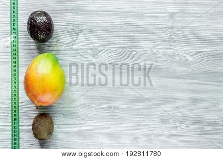 Slimming diet. Fruits mango, mangosteen, kiwi and measuring tape on grey wooden table top view.