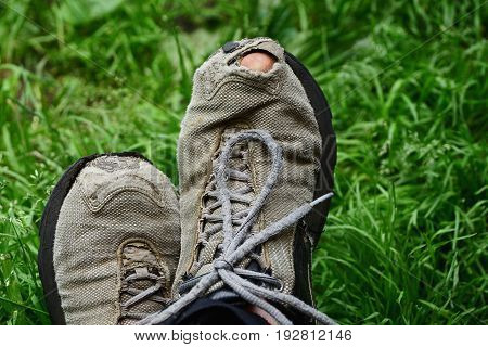 Hole on a gray sneaker on a foot in the grass