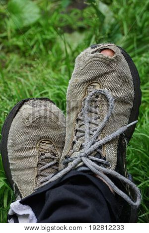 Ragged gray sneakers on legs in green grass