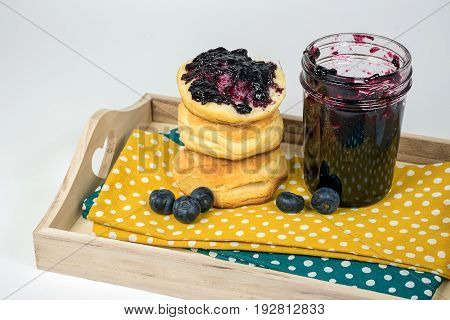 blueberry jam and bread rolls on polka dot napkin and wooden tray