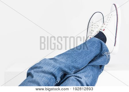 Closeup Shot of Mens Legs on White Fashion Sneakers and Jeans Laid on High Support.Horizontal Image Composition
