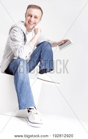 Youth Concepts. Portrait of Expressive Smiling Caucasian Man in Hoodie with Tablet Computer Sitting on Studio Box with Leg Lifted. Vertical Image