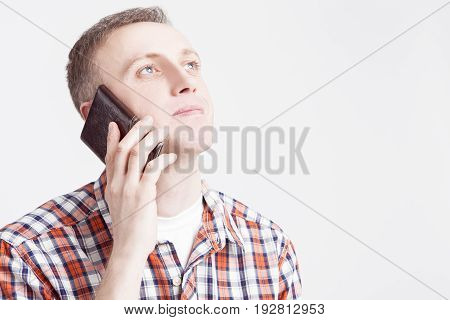 Youth Lifestyle Concepts and Ideas.Closeup Portrait of Caucasian Man Speaking on Cellphone Against White Background. Horizontal Image