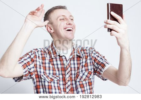 Youth Lifestyle Ideas. Portrait of Happy Caucasian Man Chatting on Cellphone During a Video Call. Posing Against White Background. Horizontal Image Orientation