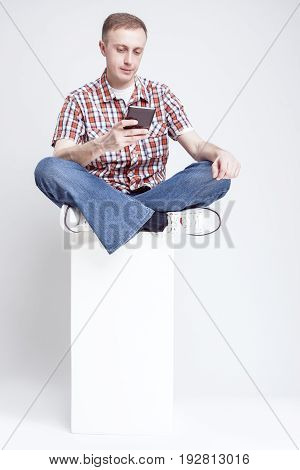 Modern Caucasian Man in Checkered Shirt and Jeans Chatting on Cellphone Against White Background. Sitting on White Box.Vertical Image Orientation