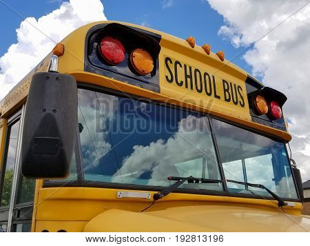 front view of yellow school bus with cloud reflection in windshield